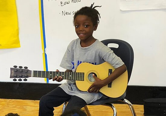 WHIN student performing on guitar